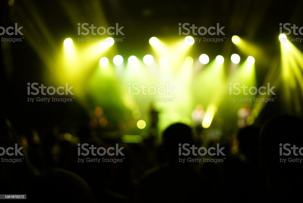 Silhouette of a big crowd at concert against a brightly lit stage....