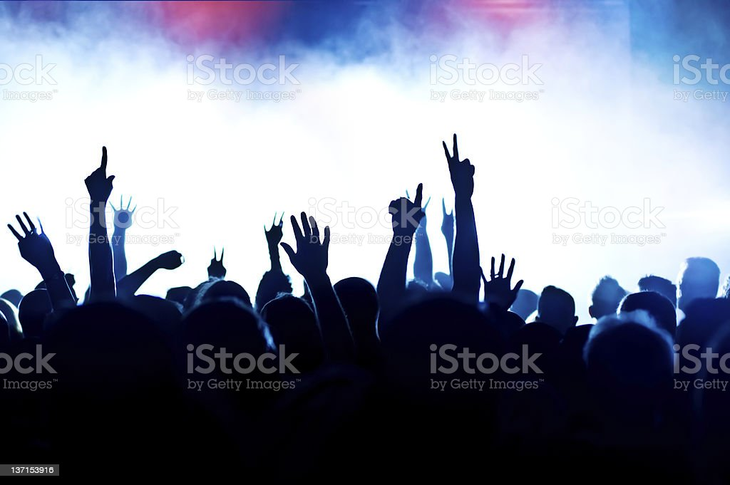 Concert crowd silhouetted by stage lights and smoke royalty-free stock photo