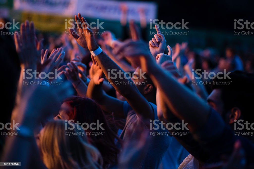 Group of people all looking in one direction with raised hands in the...