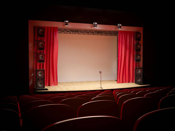Concert hall with a red curtain and a microphone on the counter. stock photo