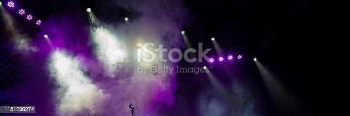istock Concert stage lighting in the fog and microphone. 1151236274