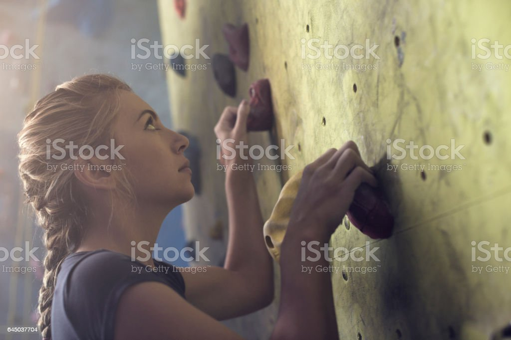 Concetrated young athlete woman hold a rock on climbing wall – Foto