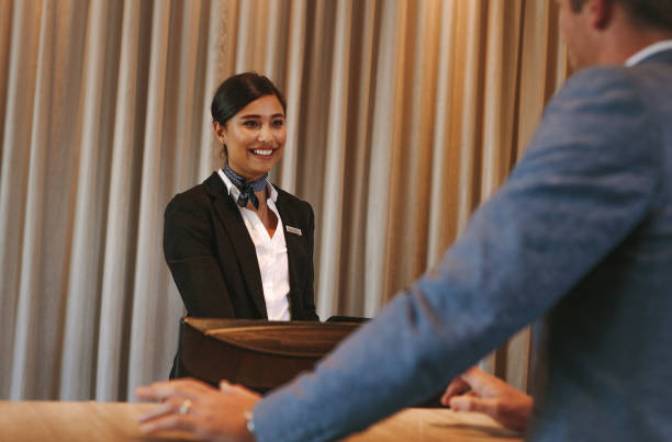 Concierge helping guest with hotel room bookings Female hotel receptionist attending a guest at reception counter. Happy female concierge helping businessman with his room bookings. concierge stock pictures, royalty-free photos & images
