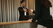 Smiling female concierge returning the documents to hotel guest after check-in process. Female client receiving her documents at hotel reception desk after check-in.