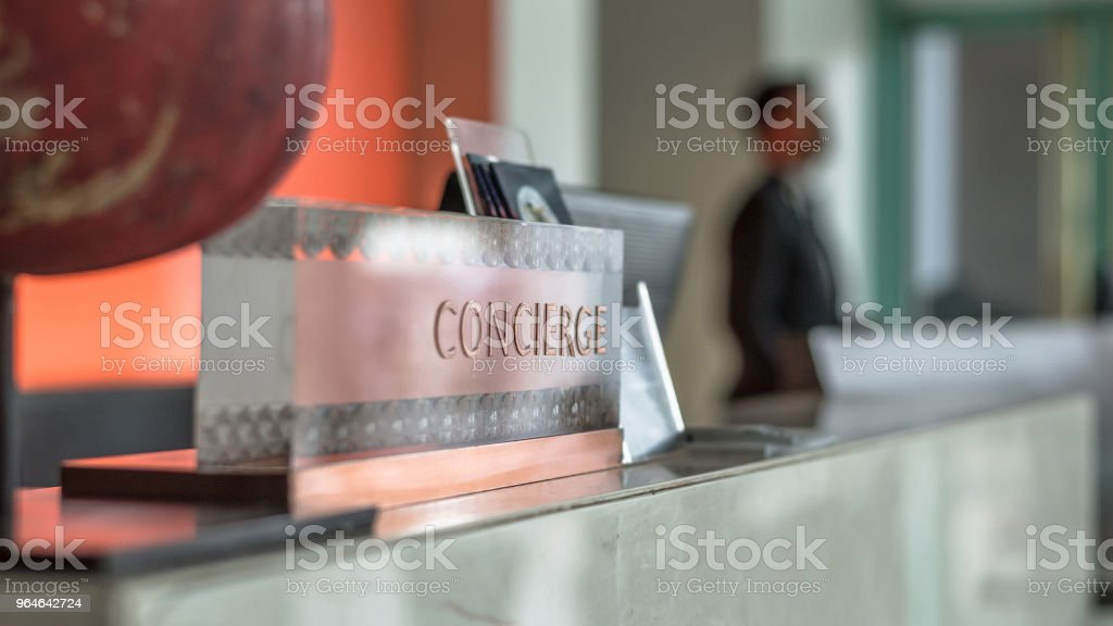 Concierge service desk counter with hotel staff team working in front of reception hall for tourist business customer royalty-free stock photo