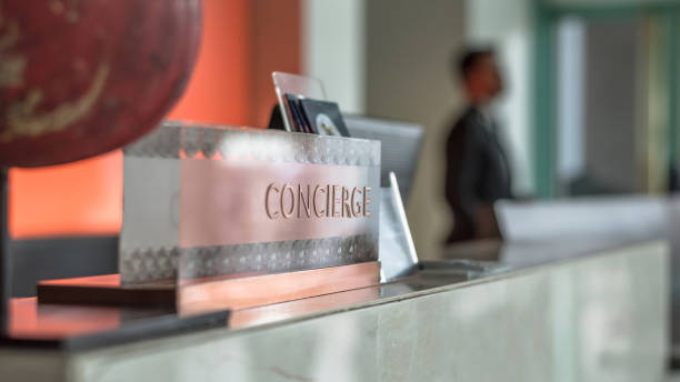 Concierge service desk counter with hotel staff team working in front of reception hall for tourist business customer Concierge service desk counter with hotel staff team working in front of reception hall for tourist business customer concierge stock pictures, royalty-free photos & images