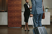 Female concierge welcoming business man at hotel lobby. Receptionist greeting guest at hotel hallway.