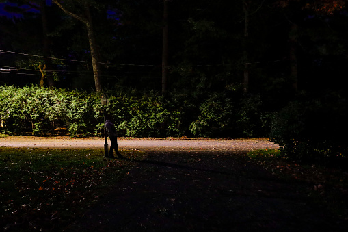 Concord, Massachusetts, USA A man stands at a lamppost on a dark residential street.