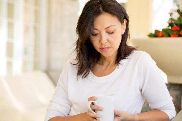Concrened woman looking worried. Concrened woman looking worried and praying on a sofa. east asian ethnicity stock pictures, royalty-free photos & images