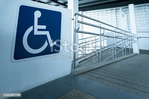 istock Concret ramp way with stainless steel handrail with disabled sign for support wheelchair disabled people. 1035083396