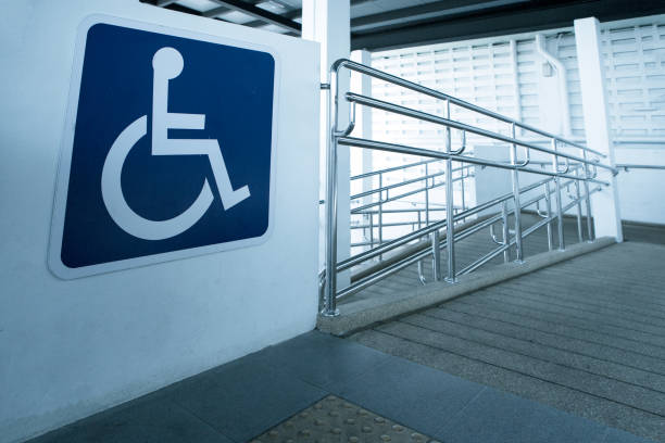 concret ramp way with stainless steel handrail with disabled sign for support wheelchair disabled people. - accessibilità foto e immagini stock