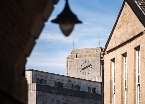 Concrete Art Deco clock tower with Roman numerals on top of retro department store in town centre viewed from under bridge archway with 1950's old out of focus street lamp hanging down.