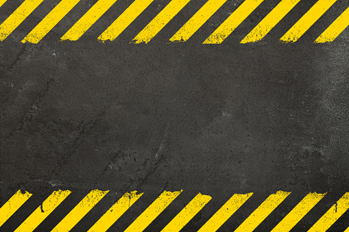 Dark grey concrete weathered wall background with yellow painted grunge hazard sign stripes and copy space