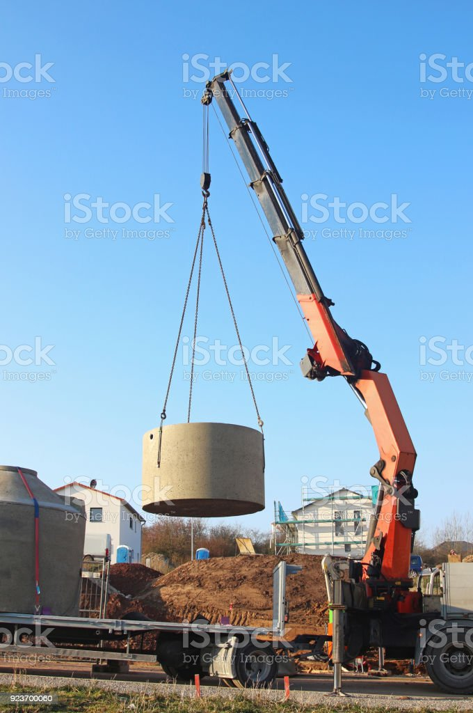 concrete cistern being lifted in the air with a crane truck stock photo