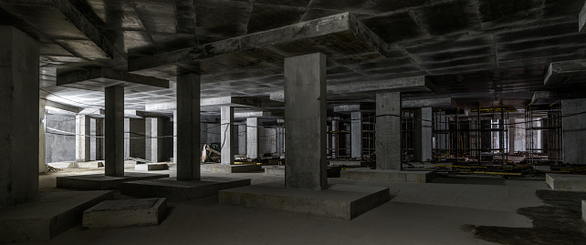 Concrete construction of basement of large building. Panorama inside the modern construction site in dark. Contemporary structure under construction with concrete walls, pillars, ceiling and floor.