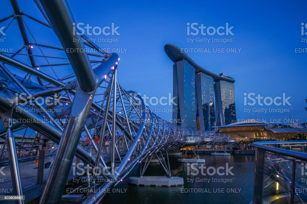 Concrete covered with stainless bridge to Marina Bay Sands Hotel during twilight time stock photo