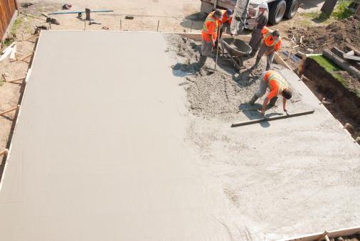Crew of concrete workers pouring and leveling a garage pad. Half of the pad is done and would make great copy space.