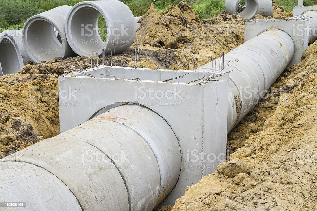 Concrete drainage pipe and manhole exposed in dirt stock photo