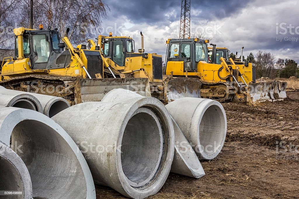 Concrete drainage pipes and bulldozers stock photo