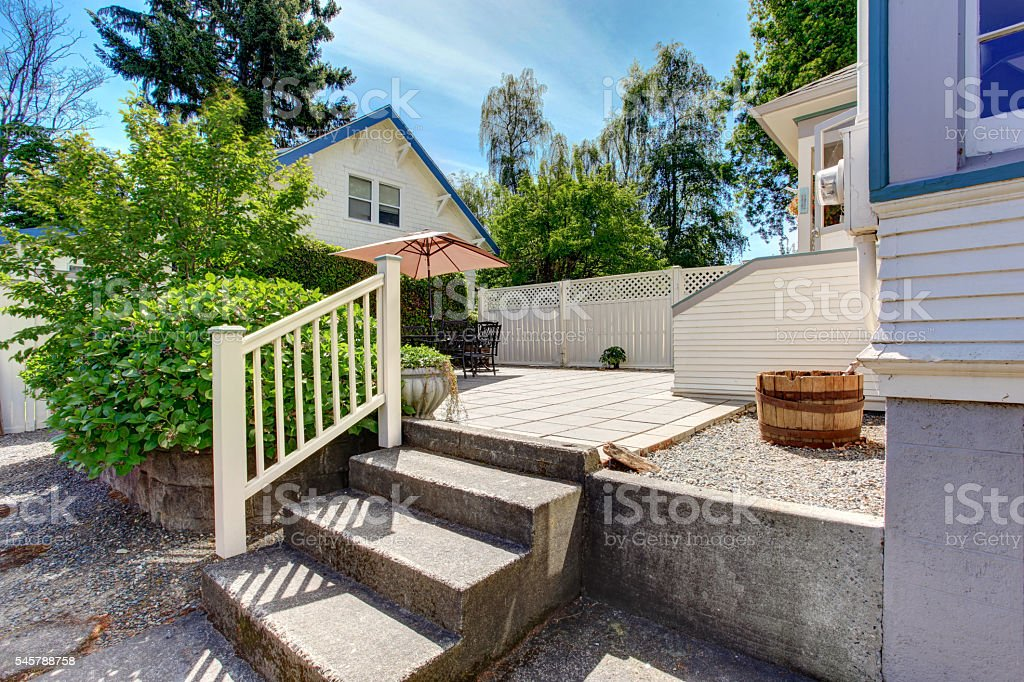 Concrete floor cozy patio area with iron table set stock photo