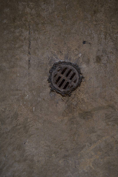 concrete floor with rusted, metal drain stock photo