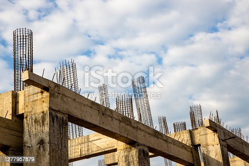Concrete foundation posts and beams and part of steel rebar cages at a construction site against blue and white cloudy sky.