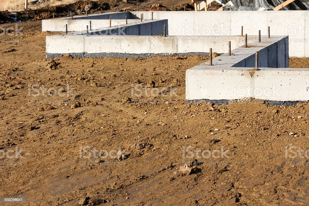 Concrete Foundation surrounded by brown soil at a construction site stock photo