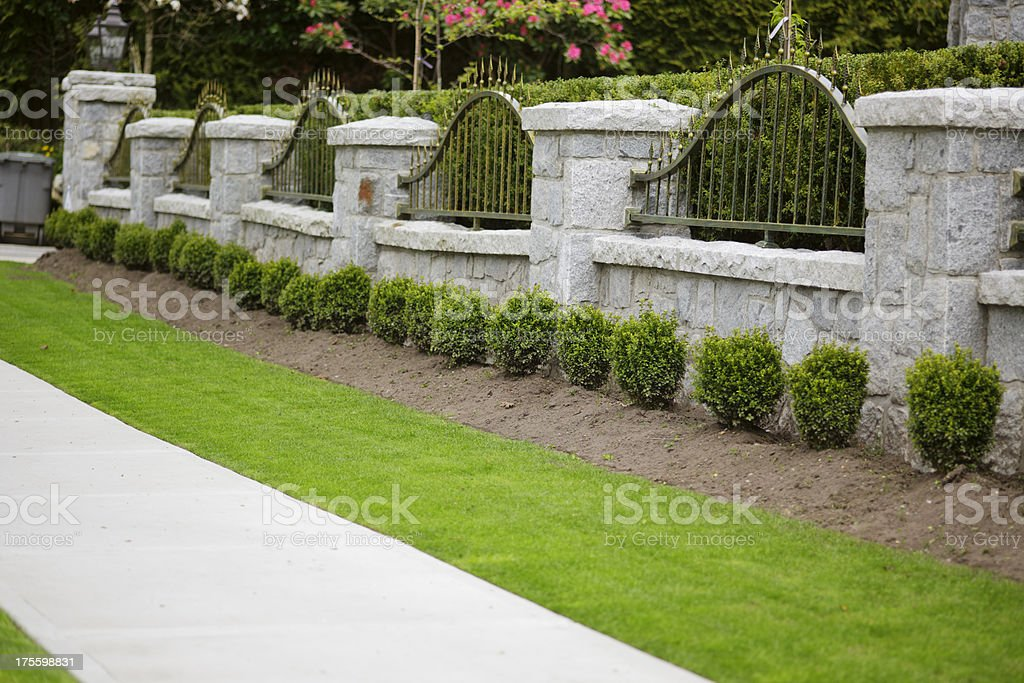 A concrete gate with metal along a well manicured yard. royalty-free stock photo