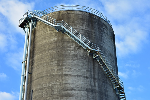 Tall industrial concrete circular silo with steel stairways up along wall leading to platform on top.
