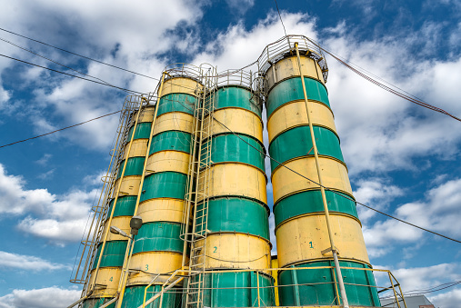 Concrete mixing plant. Four vertical towers for storing cement, the towers are painted in yellow and green stripes. Steel silos against the blue sky.