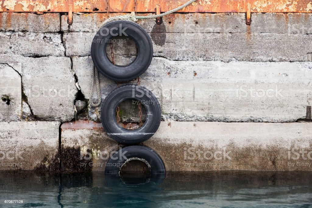 Concrete mooring wall with old used tires stock photo