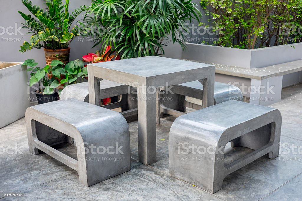 Concrete outdoor furniture set in the small garden including on table...