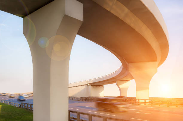 Concrete overpass from below View from below to a concrete overpass with lensflare effect elevated road stock pictures, royalty-free photos & images