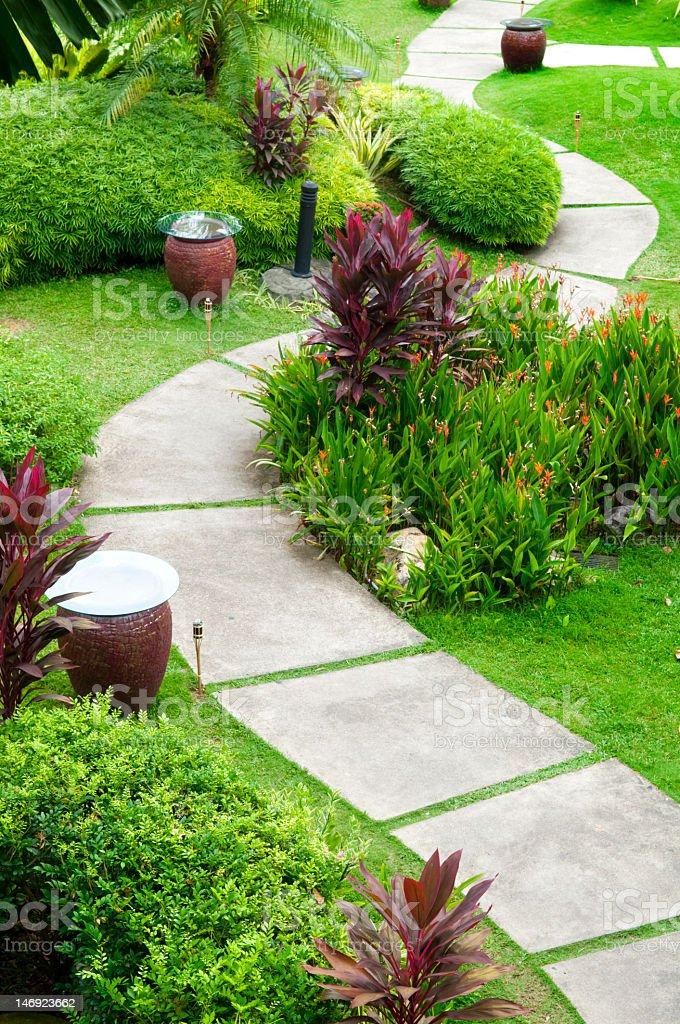 Concrete path through a green garden stock photo