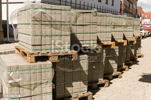 Concrete paving stones on wooden pallets at a road construction site in town
