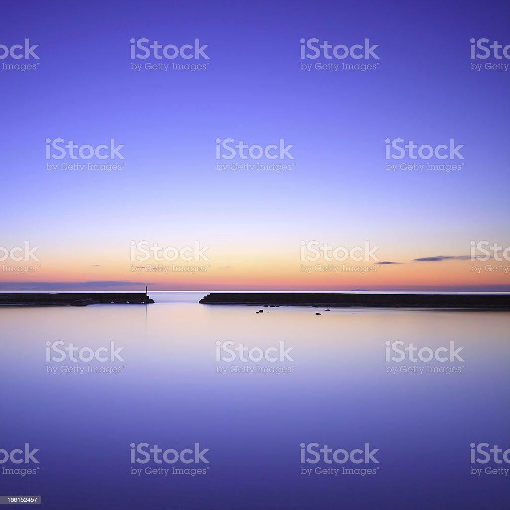 Concrete pier silhouette and blue ocean on twilight sunset royalty-free stock photo