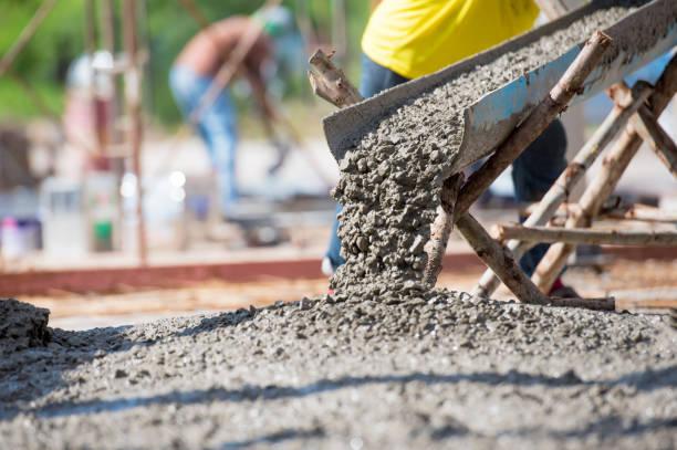 versamento di calcestruzzo durante i pavimenti di cementazione commerciale dell'edificio - calcestruzzo foto e immagini stock