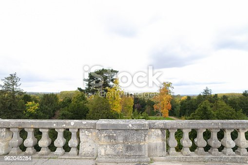 Girl sitting on concrete railing with green trees background. Concept of architectural elements.