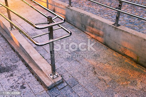666724598 istock photo Concrete ramp - driveway - for wheelchairs with a stainless steel handrail 1136043390