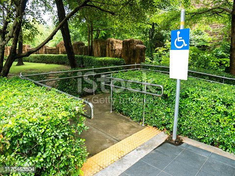 Concrete ramp way with stainless steel handrail and disabled sign for support wheelchair disabled people in the park.