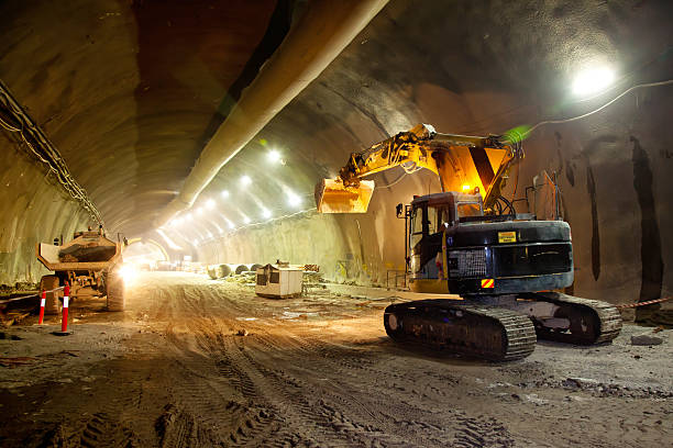 Concrete Road Tunnel Construction Excavator Concrete Road Tunnel Construction Excavator and Articulated Dump Truck construction machinery stock pictures, royalty-free photos & images