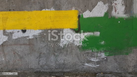 Old rough cement wall with rectangle stains of yellow and green stains. Abstract background of construction repair industry