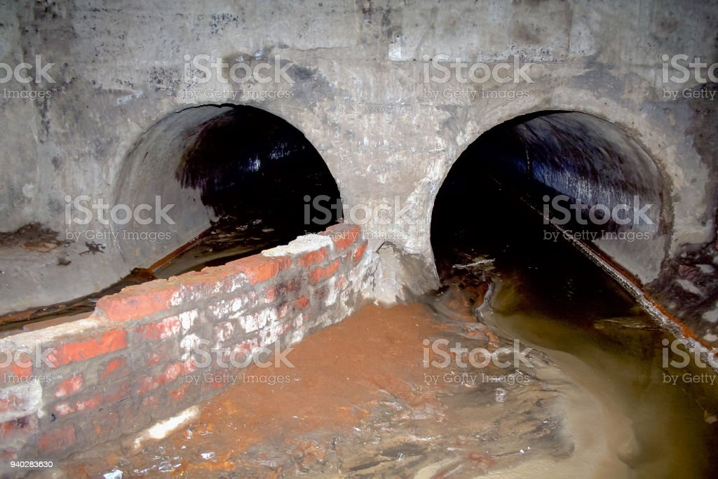 Concrete sewer pipes for waste water depart from underground gallerie stock photo