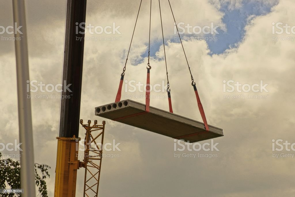 A concrete slab is lifted by a crane on a construction site stock photo