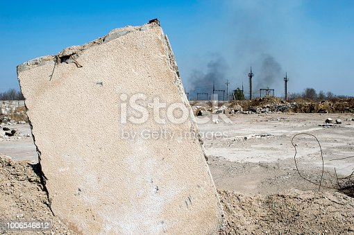 istock Concrete slab stuck in the ground against the background of a Smoking electrical substation. Background 1006546812