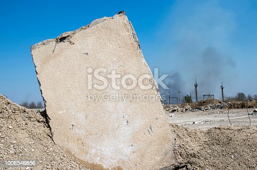istock Concrete slab stuck in the ground against the background of a Smoking electrical substation. Background 1006546856