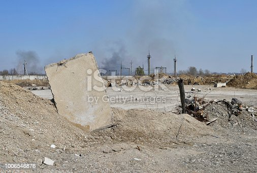 istock Concrete slab stuck in the ground against the background of a Smoking electrical substation. Background 1006546876