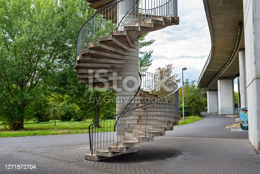 Concrete spiral staircase with metal handrails for pedestrian traffic to the bridge.