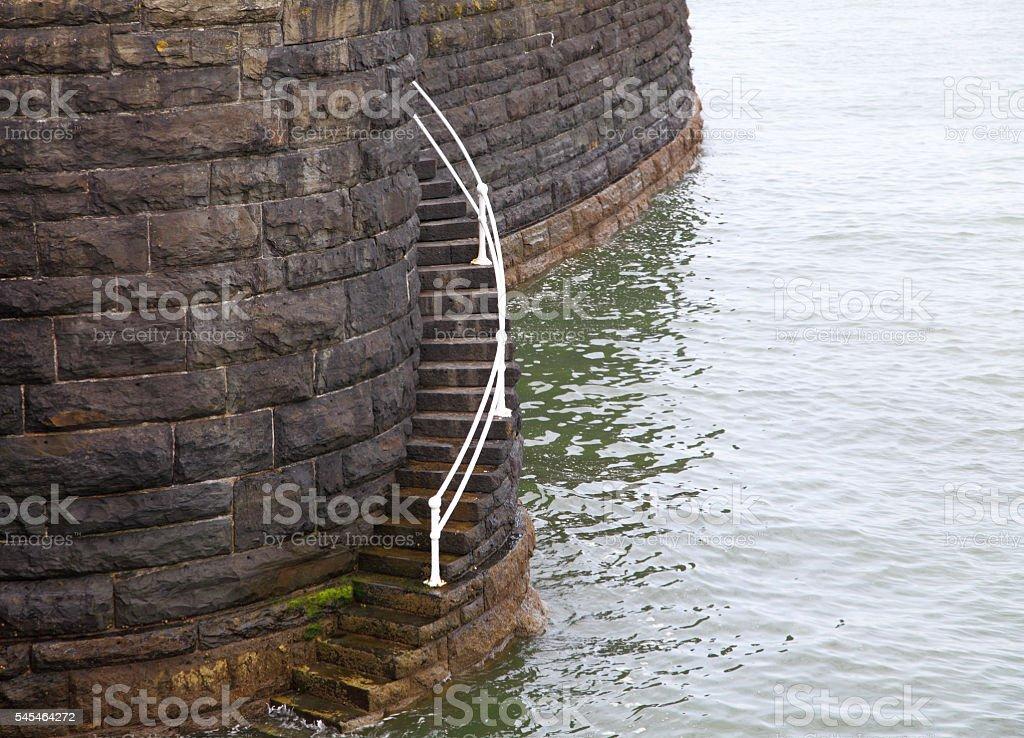 concrete steps beside sea wall stock photo