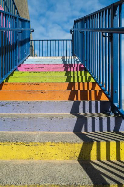 Betonstufen bemalt ebright Regenbogenfarben mit einem blauen Geländer und einem starken Schattenmuster – Foto